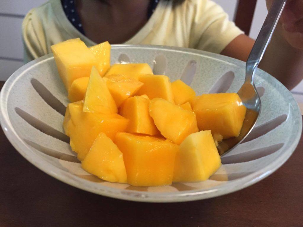 娘がマンゴーを食べている様子