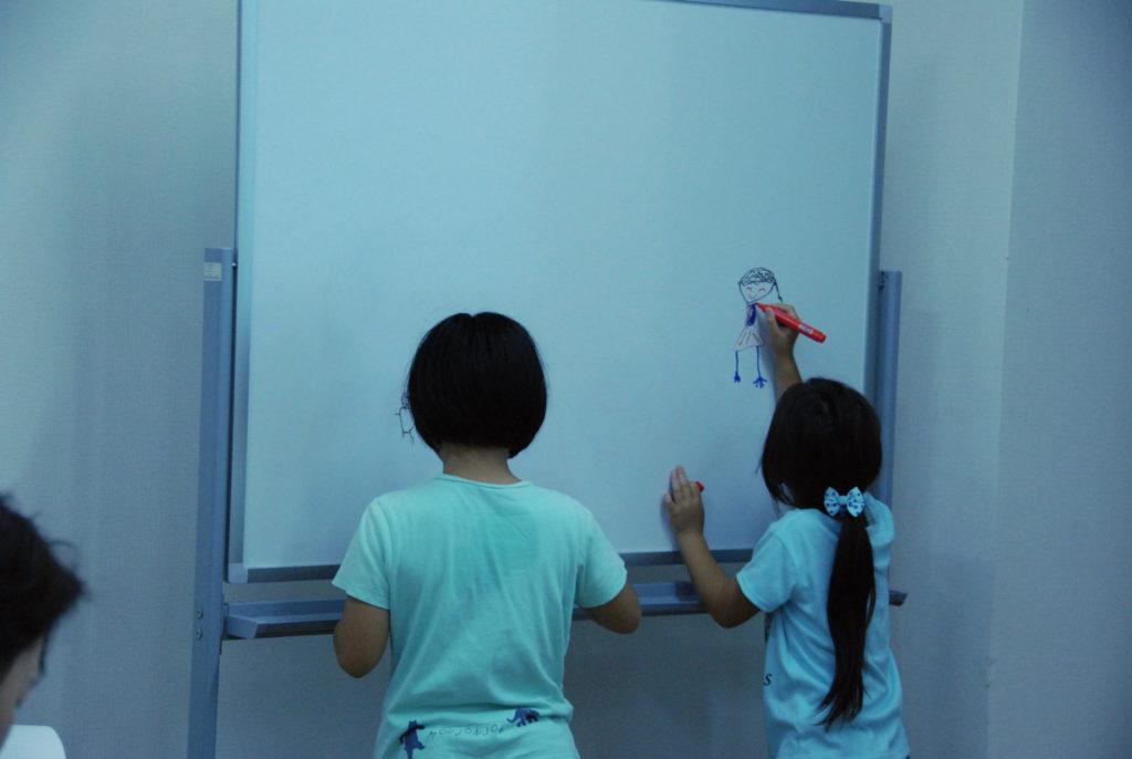 スタート前、ホワイトボードで遊ぶ子供達
